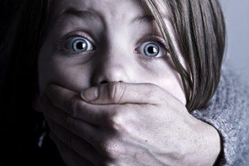 Shot of Scared Child with Hand over her Mouth